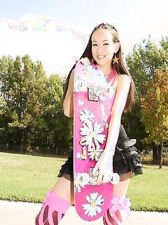 Худенькая азиатка в короткой юбке катается на скейте и показывает трусики