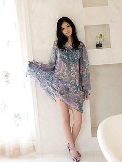 Стройная азиатка в красивом платье раздевается у окна