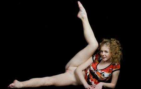 Кудрявая голая девушка в очень темной комнате показывает свое тело