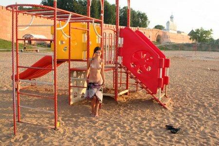 Русская девушка с красивыми сиськами гуляет голышом на детской площадке