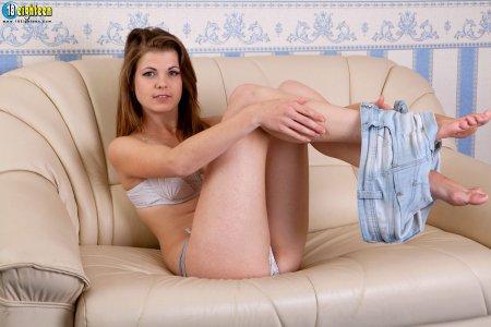 Пышнотелая шатенка с большими сиськами позирует на диване