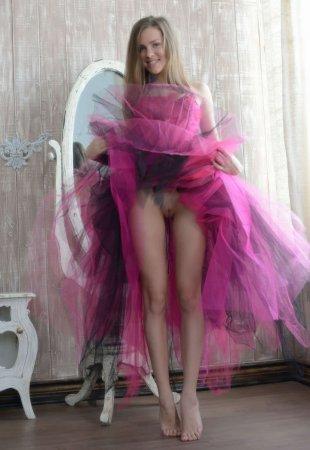 Спортивная девушка в ярком розовом платье в постели