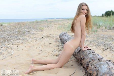 Голая девушка на пляже загорает голышом