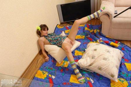 Полу голая гимнастка занимается на кроватке